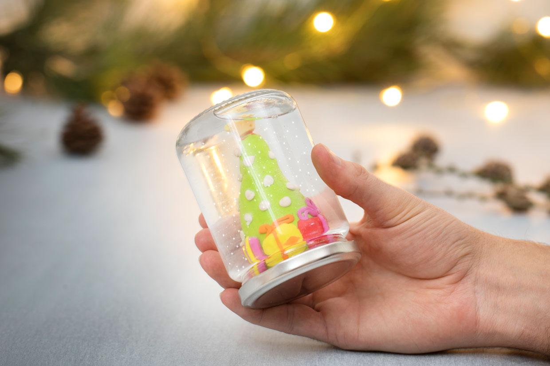 Ristekule av glass med figur av Fimo-leire og vann med glitter