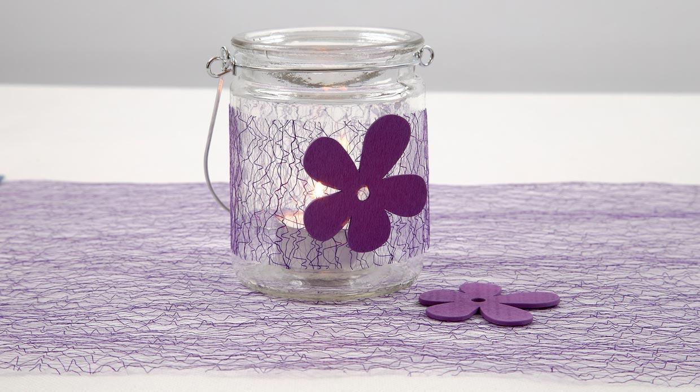 Bröllop: Ljusglas dekorerad med lila nätbordslöpare och träblommor