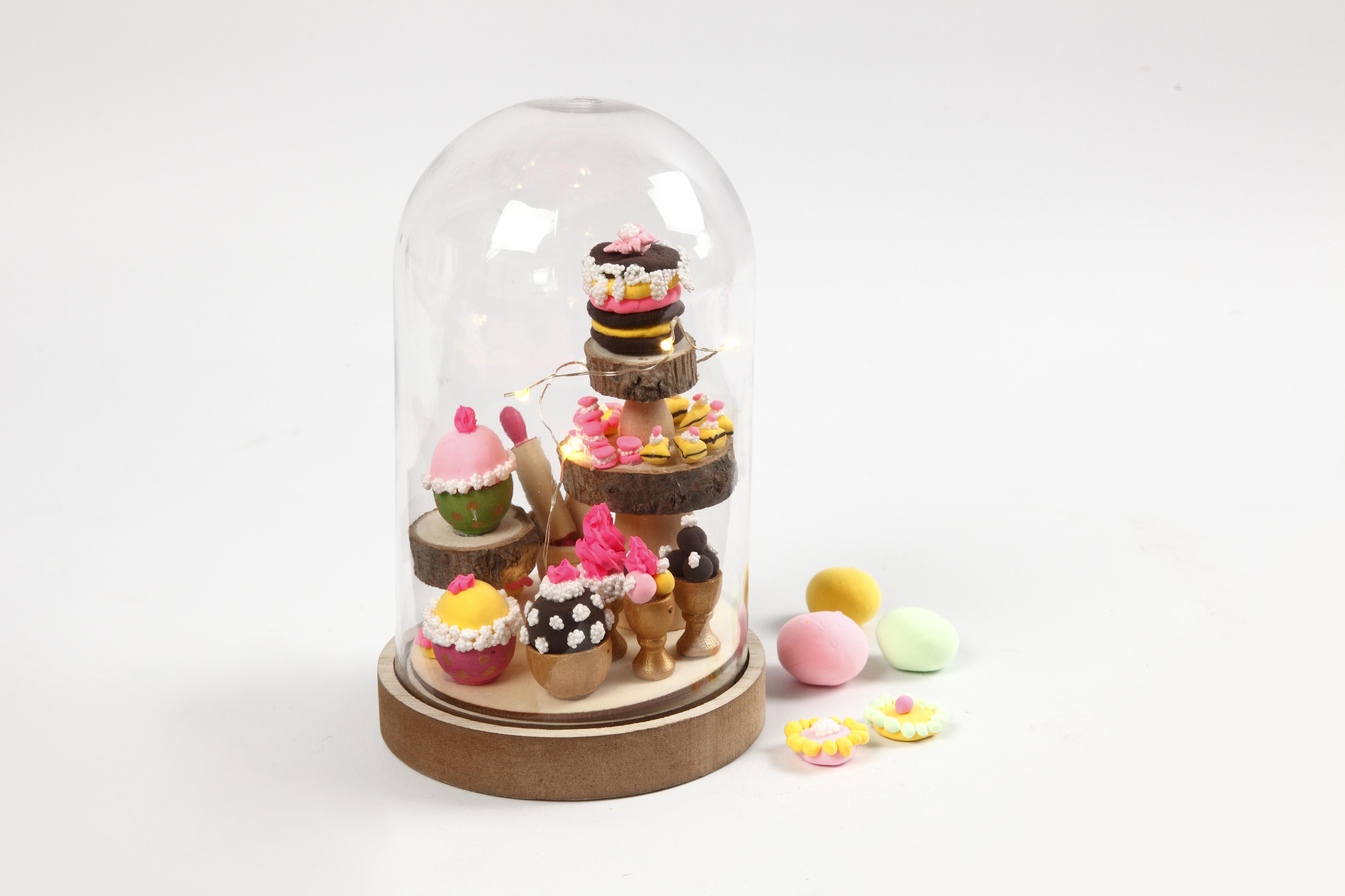Miniatyrvärld med mini cupcakes i glaskupa